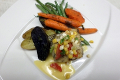 Plated Entrée: Grilled Sea Bass topped with corn relish and beurre blanc, roasted fingerlings and Japanese carrots
